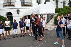 President Barack Obama hugs First Lady Michelle Obama after watching her jump…