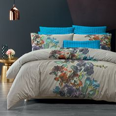 A colourful waterfall of exotic orchids creates a beautiful focal point for this serene design. Set against a neutral background of pale linen, the soft floral is given extra depth when co-ordinated with the quilted blue euro and cushion cover with tie-trim closure. The quilt cover has a plain reverse and button closure.