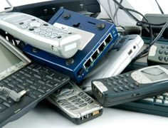 Pile of e-waste, electronics waste, including cell phones, computer keyboards, a modem, an answering machine and other technology gadgets.