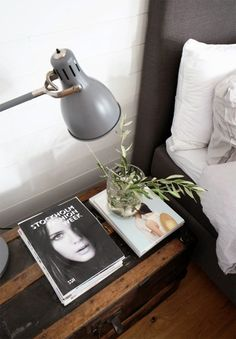 rustic bedside table, fashion books, light, leaves, gray bed, white sheets!