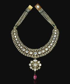 A gem-set and enamelled gold necklace, North India, 19th century. Comprising facet-cut white sapphires set in gold with foil backing, on flexible openwork chain surrounded by seed-pearl borders, hanging flowerhead-shaped pendant with spinel drop, enamelled on the reverse in red, green and white with floral details on each setting, rows of pearl-strings leading to square clasp.