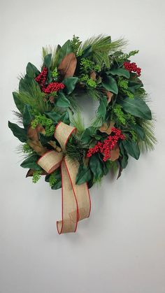 Farmhouse Christmas wreath, Artificial Christmas wreath, Magnolia and Pine Christmas wreath, Rustic Christmas wreath, Traditional Christmas wreath This is an artificial greenery wreath that almost looks fresh. It is large and full and consists of long needle pine, magnolia leaves, cedar and red berries if you so wish. This lovely wreath can be displayed all the way to spring. Measures approx. 27L x 24W x 9Deep To see all of my creations available for purchase, visit my shop through this l...