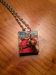 Santa scrabble tile decoupaged necklace. Find small pics in magazines and decoupage them on scrabble tiles...add lil glitter etc and a bale and chain and they are cute necklaces for gifts. Make sure to seal with a poly coat to water proof