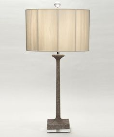 Stingray Lamp: An upright, narrow base patterned with neutral faux shagreen, the stingray leather once so highly valued for its distinctive pebbly finish, gets a boost of impact when the texture is treated with a high-contrast dual tone. The Stingray Lamp rests on a polished block foot that further nudges this lamp toward the transitional, making it a lean and luxurious piece for the desk or nightstand.