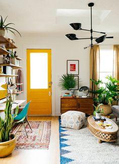 Quem disse que são só os objetos de decoração e as almofadas que ganham cores destacadas? Nessa sala de estar a porta virou protagonista, exibindo um amarelo vivo. As plantas espalhadas pelo cômodo deram um ar descontraído.