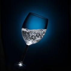 Ett glas bubbelvatten, plåtat av mig. Använde en blixt med ett raster och en blå plastfilm för att skapa den blå bakgrunden. Till att belysa vattnet tog jag hjälp av en optisk snoot som trattade ner ljuset mitt i glasets öppning.