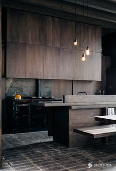 Dark and moody industrial style kitchen. Stunning timber cabinetry, black freestanding cooker and the floor looks like cobblestones!