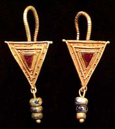 """""""ROMAN GOLD EARRINGS           II-III c. A.D.   Beaded, hooked ear wire soldered to a triangle shield with beaded wire frame. Additional beaded wire and granulation around a triangular garnet bezel-set in the center. Solid wire with three blue glass beads suspended from the bottom corner of the shield. L. 41 mm"""""""