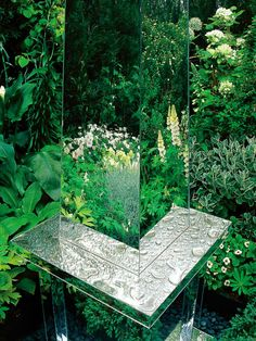 Using mirrors is a clever way to double the effect of flowers by giving the illusion of space. In this garden, a mirrored oblisk becomes the focal point and reflects the flowers in bordering beds.
