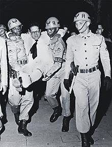 Lacerda, baleado no pé, é amparado por policiais. Começava a crise política de Getúlio Vargas