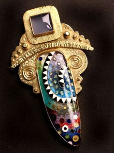 An intricately designed gold brooch with bezel set gemstone. The square flecks in the blue section of the enamel are snipped bits of 24kt gold cloisonne wire layed flat for even more details and glimmer. By Michael Romanik, a local...