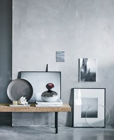 A collection of black and white pictures arranged by a gray wall