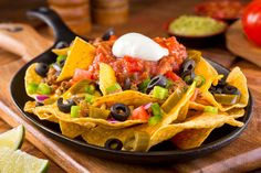 a plate of delicious tortilla nachos with melted cheese sauce ground beef jalapeno peppers red onion green onions tomato black olives salsa and sour cream with guacamole dip. Tortilla Nachos, Tortilla Chips, Beef Nachos, Mexican Dishes, Mexican Food Recipes, Nachos Mexicanos, National Nacho Day, How To Make Nachos, Vegetarian