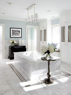 Beautiful Bathrooms * Unique bathtub placement in a marble surround, marble floors with interesting tile inlay, pretty pendant lighting, dual linen cabinets and soothing blue wall color.