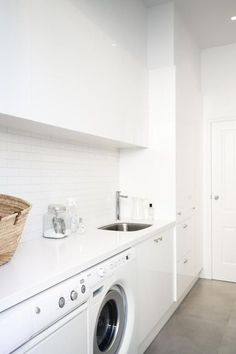 Sleek modern laundry room features white lacquer cabinets accented with polished nickel hardware alongside white washer and dryer next to sink with off-set deck faucet.