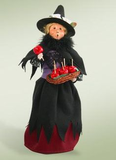"""Everyone loves a witch that gives out treats! Especially a Halloween standard . . Candy apples.  This retired Byers Choice Caroler Witch has a feather boa, a black cape and apron and lilies on her witches hat. She carries a wicker basket full of shiny red Candy Apples.  Approximately 13"""" tall."""