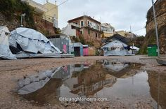 """Global Refugee Crisis Greece - The Souda refugee camp on Chios island Greece during a recent rainstorm. The fabric tents have been """"winterized"""" against the freezing elements by merely covering them in UNHCR plastic tarps. Water seeps into the fabric tents from all directions including from under the fabric floor leaving blankets bedding clothes and other items continually wet and cold. The plastic tarps also prevent the tents from drying out in the sun during the day. Souda houses…"""