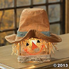 Scarecrow Glass Block Lamp. This fun scarecrow wears a felt hat and a glowing grin. Place him among your fall decorations to cast a glow on your Thanksgiving celebration. Cord with on/off switch. 10H x 9W.  Terry's Village