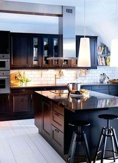 """Pierre naturelle. Les façades de cette cuisine """"Faktum"""" sont habillées de portes """"Ramsjö"""" brun noir mat. L'îlot est surmonté d'un vaste plan de travail dessiné sur mesure, en poudre minérale résistant aux taches et aux rayures (""""Personlig""""). 539 € l'implantation type, Ikea."""