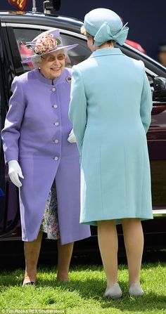 The Queen is greeted by Julia Budd, the director of Epsom Downs racecourse, who wears a pale blue coat and nude shoe