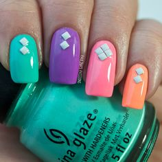 Colorful nails with white studs.