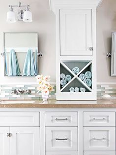 This bathroom pairs smart storage and soothing colors, and it boasts a charming coastal-cottage style. A large central cabinet with open cubbies for towels offers more useful storage space than shallow medicine cabinets would have provided. Below the countertop, a mix of drawers and standard cabinets offers versatile storage. White Shaker-style cabinets offer a classic look, while a low backsplash of subway tile in soft blues and greens melds vintage style with coastal hues.