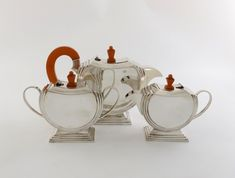 An Indian three-piece Art Deco tea set, by Narotamdas Bhau, Bombay, circular geometric form, amber coloured bakelite handles and finials, on raised stepped rectangular bases, length handle to spout 25cm, approx. weight 37.5cm.