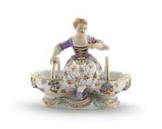 A Meissen sweetmeat figure 19th century, modelled as a girl seated between two baskets applied and painted with flowers, holding a posy of flowers in her left hand, blue crossed swords mark, 14.5cm across.