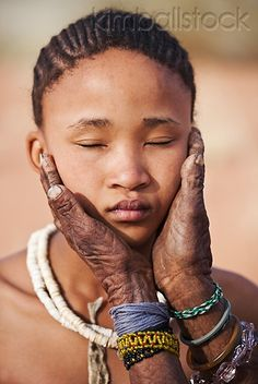 Africa | Elderly San Woman's Hands Embracing Young Girl's Face. Namibia | © Martin Harvey