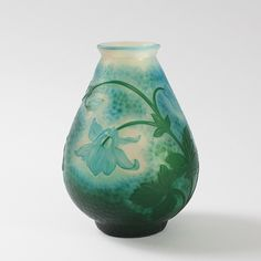 This is not contemporary - image from a gallery of vintage and/or antique objects. French Wheel Carved Vase by Daum  A French Art Nouveau wheel carved vase by Daum, featuring light blue columbine flowers with dark green stems and leaves against a blue and green ground.