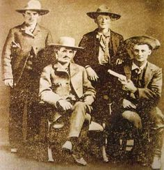 The photograph on left is one of the few known photographs of Sam Bass. This photo was taken in Dallas, Texas in 1876. The men seated are Joe Collins (left) and his brother Joel Collins (right). Sam Bass is standing (left) and John E. Gardner is standing (right). The photo is courtesy of Robert G. McCubbin, Jr.