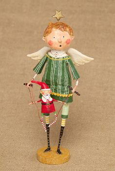 """Lori Mitchell - Christmas Puppeteer Angel - Wooden Duck Shop Size:  9.5"""" Inches  This adorable boy angel has wings and a star balancing on his head!  His legs have the trademark Lori Mitchell stockings with crazy colors and stripes!   He is holding a Santa Claus marionette that also has red and white striped stockings!"""