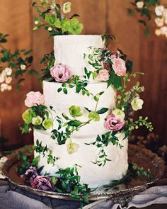 A Fun-Filled Farm Wedding in Tennessee | Martha Stewart Weddings - Flowers encircled raspberry-lemon, chocolate-mocha, and carrot-cake tiers coated in vanilla buttercream made by Magpies Cakes.