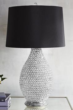 We think this Black & Crystal Bead Table Lamp from Pier 1 is absolutely stunning. Countless crystal beads are individually strung to create this lamp's brilliant vase, allowing you to see its outer form and inner beauty. The black satin shade, lined with reflective silver, is topped with a faceted crystal ball finial to focus its allure. Is it working?