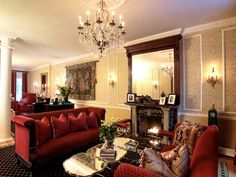 Two plush red sofas face each other in this luxurious living room divided by a tri-cut mirrored coffee table. A large dark-stained wood mirror over the fireplace breaks up the tan patterned wallpaper and white molding on the walls. Each sofa is covered with red and gold accent pillows while a crystal chandelier and traditional sconce lights give added elegance to the space.