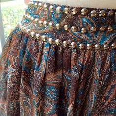 Fun brown paisley flowy skirt This skirt is so boho fun! Light chiffon paisley print overlay has brown lace hem, lightweight cotton lining. Waist is embellished with goldtone nailhead accents in front, elastic stretch in the back-fits a range of sizes! Rue 21 Skirts