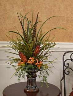 Grasses, Feathers and Protea Mantel Floral Design NC136. Whistful grasses accented with feathers and Proteas in lovely resin pedestal vase. Great Mantel Design 14W x 28H