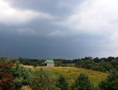 The White Pine Cabin with a summer storm coming in the distance. The rain falling on the tin roof is hypnotic! Come see for yourself! www.hockinghillsfarm.com
