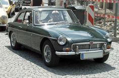 Early MGB GT. The early cars are the more desirable with wire wheels, chrome bumpers /grill and leather seats.