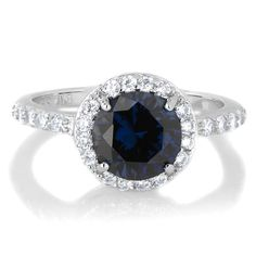 Silvertone September Imitation Birthstone Ring - Blue CZ. Celebrate life with a Sterling Silver Imitation Birthstone Ring!. Imitation Birthstone rings are the perfect way to gift someone something special on their birthday. This September SimulatedSapphire CZ ring features a 2 carat round cut stone that is surrounded by petite size clear stones giving off the angelic halo effect. Smaller size CZs extend partially down each side of the band for even more radiance. Sparkle in style during…