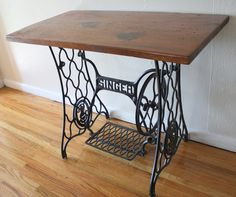 This is an antique Singer sewing machine iron table base that has been reclaimed and mounted with a wood top. The iron table base has a pedal that presses down, and a corresponding wheel that tur…