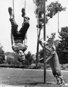 Sobre 1945: Un niño cuelga boca abajo en un columpio mientras otro se agarra a una barra. (Foto de Lambert/Getty Images)