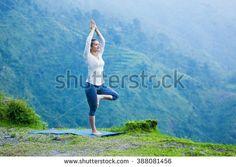Woman practices balance yoga asana Vrikshasana tree pose in Himalayas mountains outdoors. Himachal Pradesh, India. Panorama