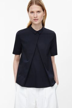 Made from crisp stretch poplin, this lightweight shirt has a pleated front for a modern flared shape. Fitted at the shoulders, it is a buttonless style with a narrow pointed collar, short sleeves and a hidden zip fastening along the back.