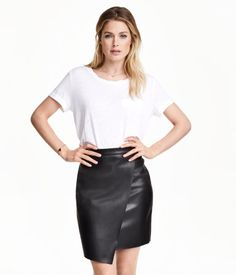 Short skirt in imitation leather with an attached wrap front. Concealed zip at back. Unlined.