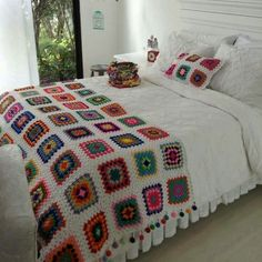 Crochet elaborada por Guela Mainieri That room looks so relaxing the white walls, The garden outside, and the beautiful colorful crochet . Crochet Square Blanket, Crochet Square Patterns, Crochet Squares, Crochet Blanket Patterns, Crochet Granny, Crochet Bedspread, Crochet Cushions, Crochet Home Decor, Crochet Crafts