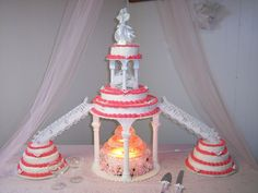 Doves & Wedding Bands: 3 Tier with Fountain ...Stairs on each side going  to 3 layer cakes - This one is 3 tiers in the middle.... then stairs going down both sides, leading to a 3 tier/layer Cake.  They wanted the Middle cakes to be WHITE, the ones on one side Chocolate, and the ones on the opposite side Strawberry.  There are white doves with pairs of gold wedding bands in various spots around these cakes!