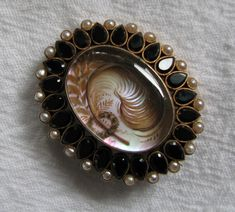 1870 Mourning brooch  Set with jet and pearls, this is an exceptionally pretty pin. The hair is arranged as a feather through a wreath and with leaves. It's all hair. The back is inscribed M. B. Barrett 1819 - 1869. Pearls and jet both had great symbolism for the Victorians. The pearls signified tears.