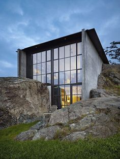 This minimalistic concrete retreat nestled into a rock designed by Olson Kundig Architects is located on the island of San Juan in  the state of Washington.