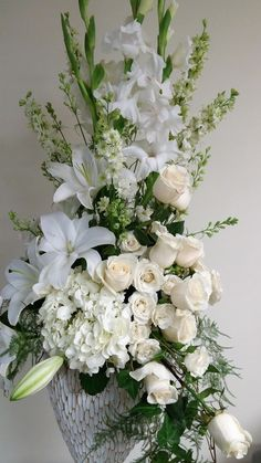 Tall white arrangement, White gladiolus, White oriental lilies, white roses, white hydrangea, white spray roses, and white larkspur